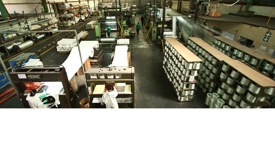 floor of factory with machines and reels of fabric